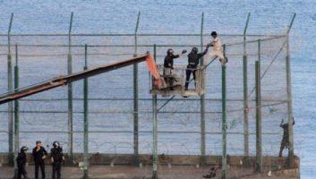 Des migrants subsahariens franchissent la barrière frontalière séparant le Maroc et Melilla
